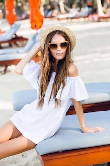茶色のサングラスと麦わら帽子のかわいい女の子が広く笑顔し、手で帽子を握る