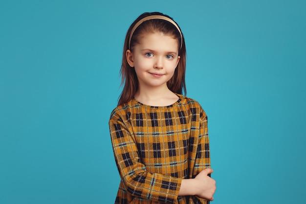 Милая девушка в клетчатом платье серьезно смотрит в камеру, стоя в одиночестве
