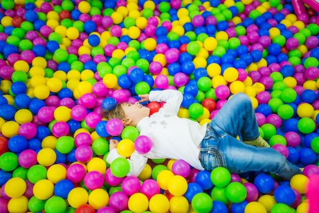 어린이 옷에 귀여운 소녀는 서로 다른 색상의 밝은 플라스틱 공으로 수영장에서 활약