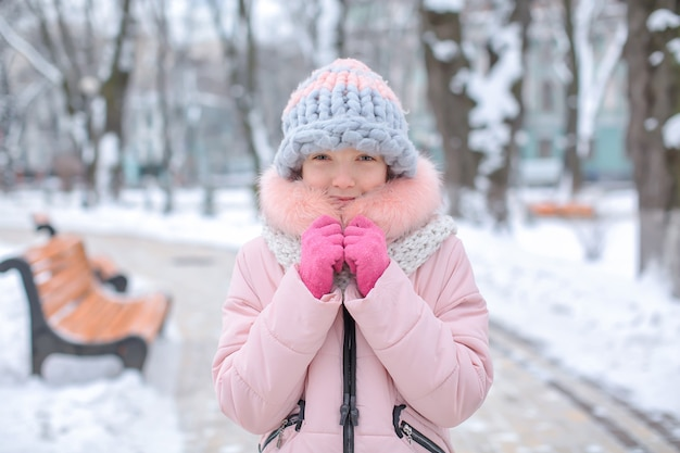 겨울 방학에 차가운 눈 덮인 공원에서 귀여운 소녀