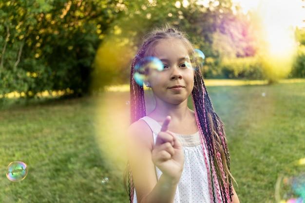 Милая девушка в платье и африканских косичках стоит в парке на фоне мыльных пузырей и