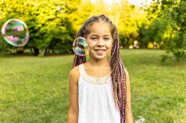 Милая девушка в платье и с африканскими косичками стоит в парке на фоне мыльных пузырей
