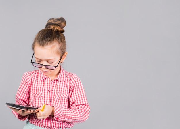 Милая девушка в очках с помощью планшета