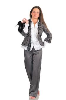 Милая девушка в сером костюме смешно позирует, стоя на одной ноге и держит в руках туфли. вся длина