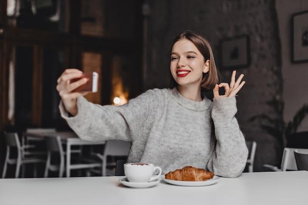 灰色のセーターを着たかわいい女の子がカフェで自分撮りをしてokを表示します。赤い口紅の女性がコーヒーとクロワッサンを注文しました。