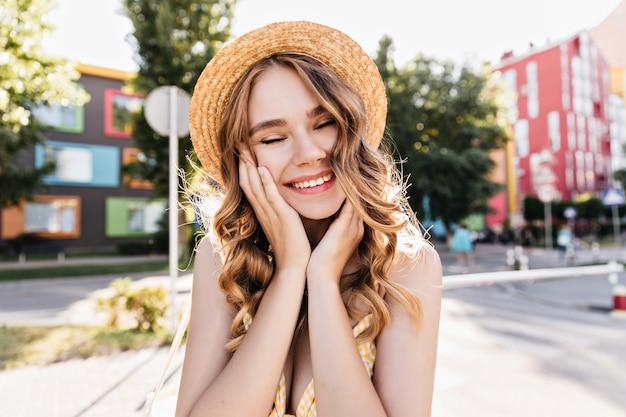 街に目を閉じて笑っている帽子のかわいい女の子。夏の朝に夢のようなポーズをとるロマンチックな白人女性。