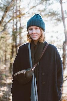 流行に敏感なかわいい女の子が森の中で屋外を見て