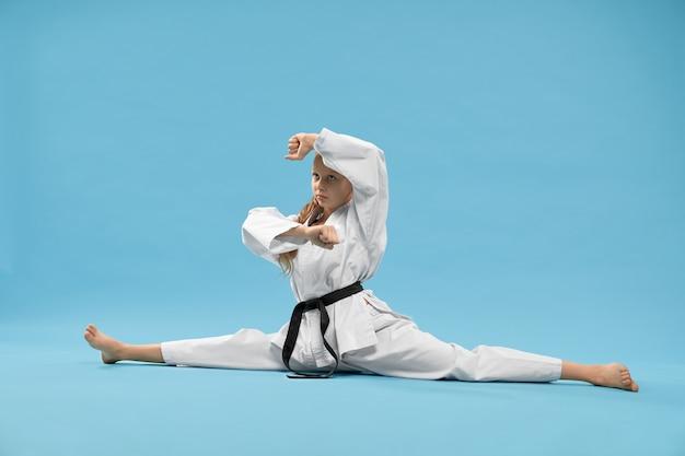 Милая девушка в кимоно, сидя на продольном шпагате в студии