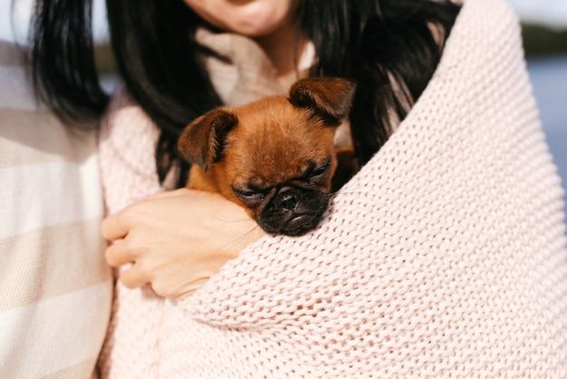 가벼운 옷에 귀여운 소녀는 그녀의 팔에 그녀의 작은 강아지를 보유