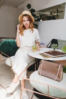 長いスカートと白いスニーカーでかわいい女の子がカフェで冷やして、喜びでカクテルを飲みます
