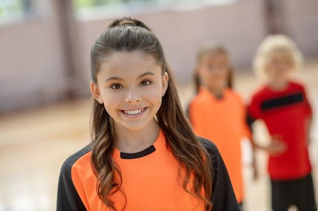 素敵な笑顔のオレンジ色のtシャツのかわいい女の子