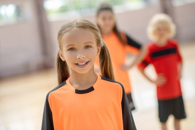 積極的に笑っているオレンジ色のtシャツのかわいい女の子