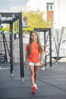 オレンジ色のtシャツを歩いて笑ってかわいい女の子