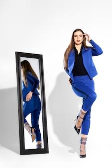 거울 근처 pantsuit와 얇은 명주 그물 양말에 귀여운 소녀