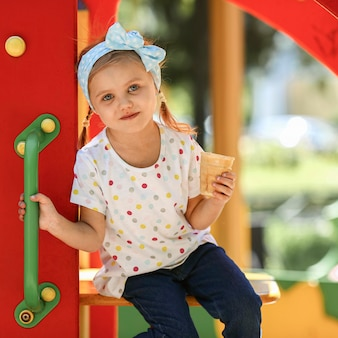 Милая девушка в парке ест мороженое