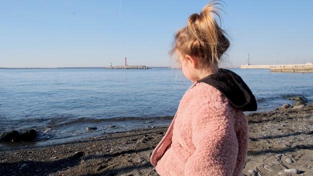 Милая девушка в розовой куртке смотрит на спокойное море с пляжа
