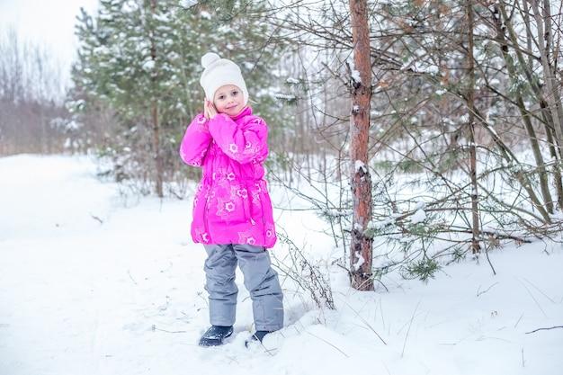 冬の森で遊んで、冬の屋外で時間を過ごすピンクの暖かい服を着たかわいい女の子
