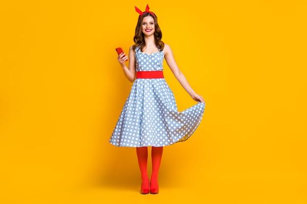 폴카 도트 드레스 빨간 스타킹에 귀여운 소녀는 노란색 배경에 핸드폰을 잡아