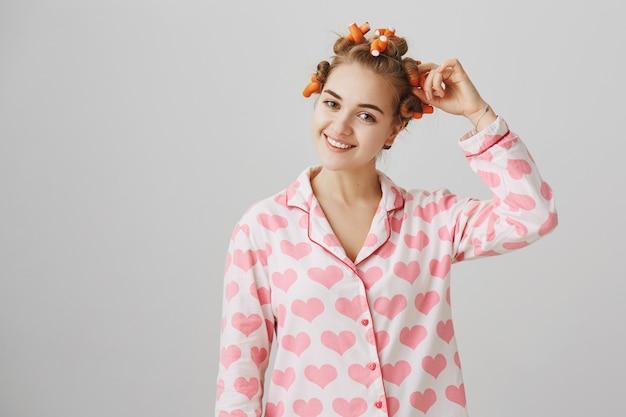 パジャマでかわいい女の子はヘアカーラーを適用します