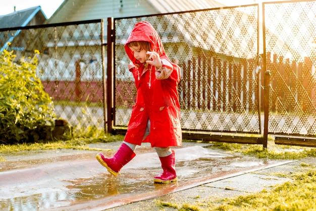 赤いジャケットを着たかわいい女の子が水たまりにジャンプしています。暖かい夏や秋の太陽が沈む。村の夏。