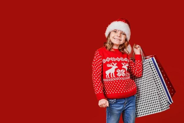 ショッピングバッグを保持している赤いセーターのかわいい女の子