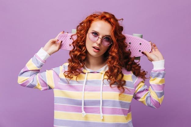 라일락 벽에 핑크 스케이트 보드와 함께 포즈 라운드 선글라스에 귀여운 소녀