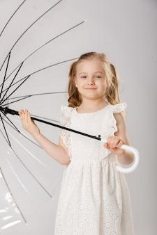 透明な傘の下でゴム長靴のかわいい女の子