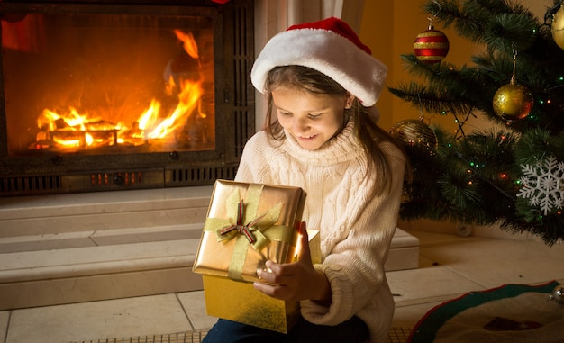 Милая девушка в шляпе санты сидит у горящего камина и смотрит в рождественскую подарочную коробку