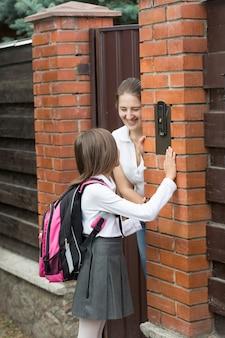 초인종과 어머니가 문을 여는 학교 유니폼 울리는 귀여운 소녀