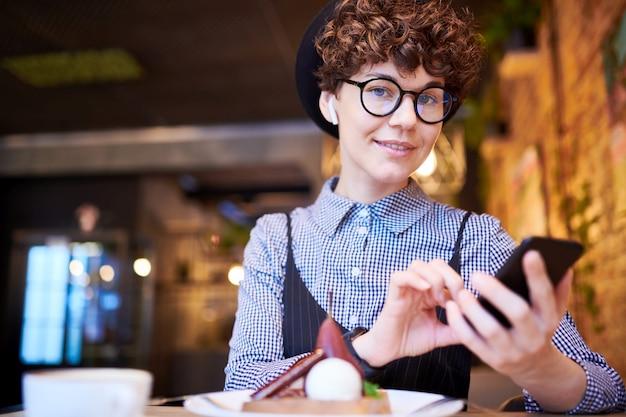 Милая девушка в элегантной повседневной одежде, шляпе, аэродромах и очках смотрит в плейлист в смартфоне, сидя в кафе