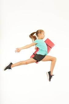エクササイズマットを保持し、空中ジャンプしながら目をそらしているスポーツウェアのかわいい女の子。白い背景で隔離