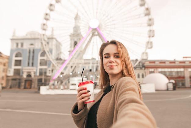 Симпатичная девушка в весенней одежде, в пальто, держит чашку кофе в руке и делает селфи на фоне улицы