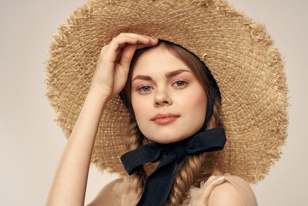 黒のリボンとベージュのドレスと麦わら帽子のかわいい女の子