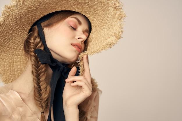 Милая девушка в соломенной шляпе с черной лентой и платье
