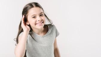Cute girl in studioshowing hearing sign