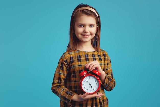 Милая девушка в стильном платье улыбается и держит будильник на синем фоне