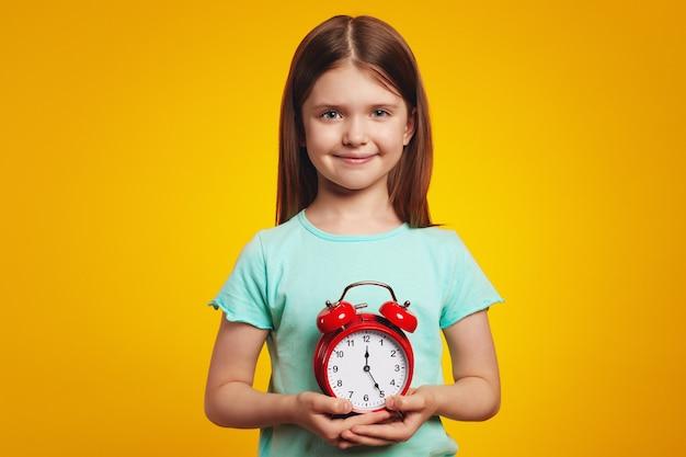 Милая девушка в стильном платье улыбается и держит будильник на желтом
