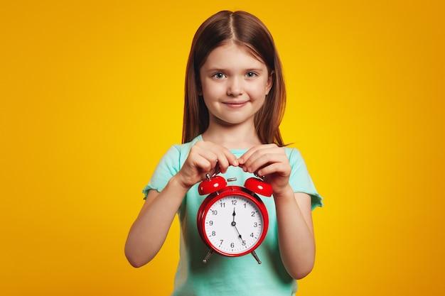 Милая девушка в стильном платье улыбается и держит будильник на желтом фоне
