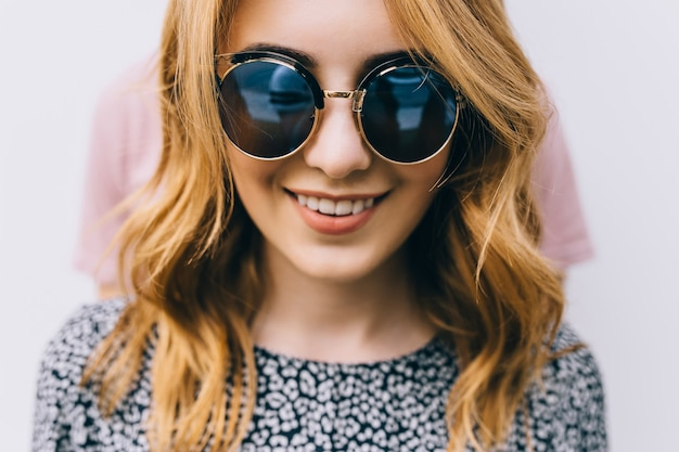 Милая девушка в солнцезащитных очках крупным планом улыбается