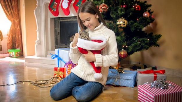 Милая девушка в свитере позирует с серым котенком под елкой