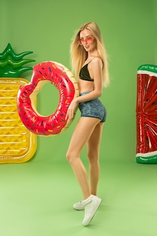 インフレータブル水泳サークルでスタジオでポーズをとる水着のかわいい女の子。緑の夏の肖像画白人ティーンエイジャー