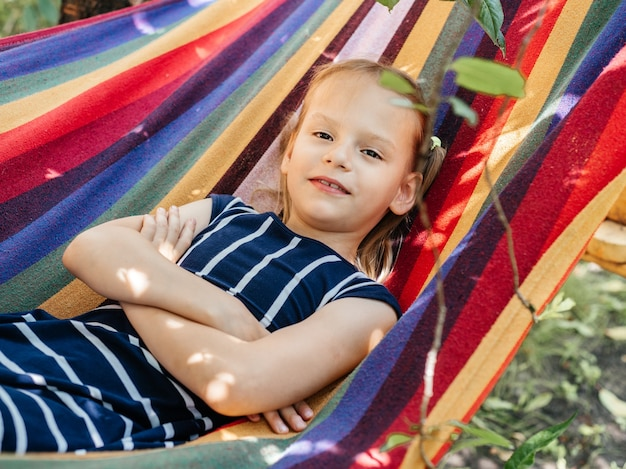 Милая девушка в красочном гамаке на летнем фоне, летние каникулы на открытом воздухе