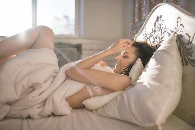 침대에 아침에 귀여운 여자는 흰색 란제리에 놓여