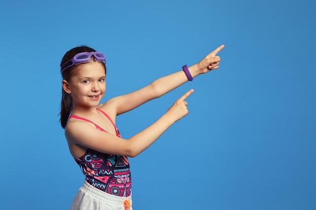 Милая девушка в модном купальнике и плавательных очках, указывая обеими руками