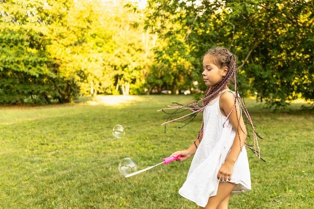 Милая девушка в белом платье и с африканскими косичками пускает мыльные пузыри в парке и весело ловит рыбу