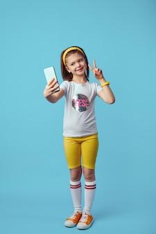 Милая девушка в белой футболке делает селфи на мобильном телефоне, показывая жест мира