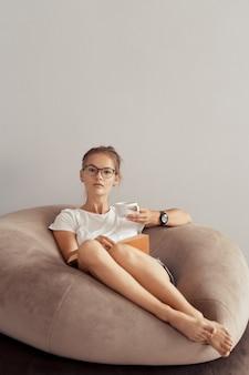 Милая девушка пьет кофе и читает книгу дома