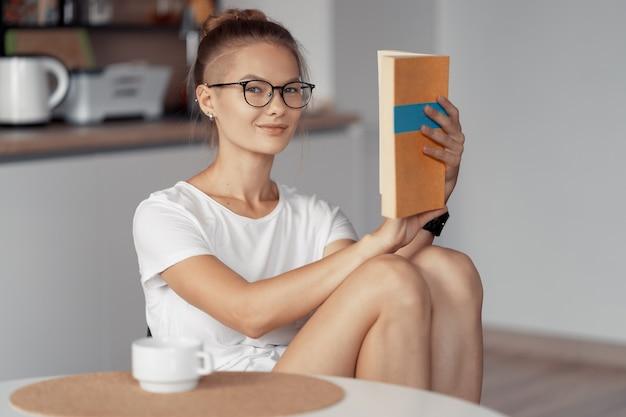 Милая девушка пьет кофе и читает книгу за кухонным столом дома