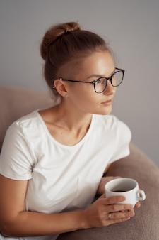 Милая девушка пьет кофе дома