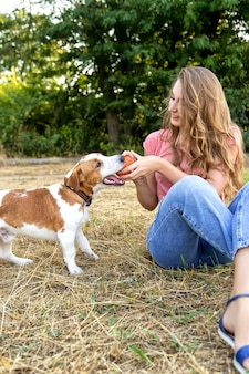 Cute girl is playing with her dog in the park